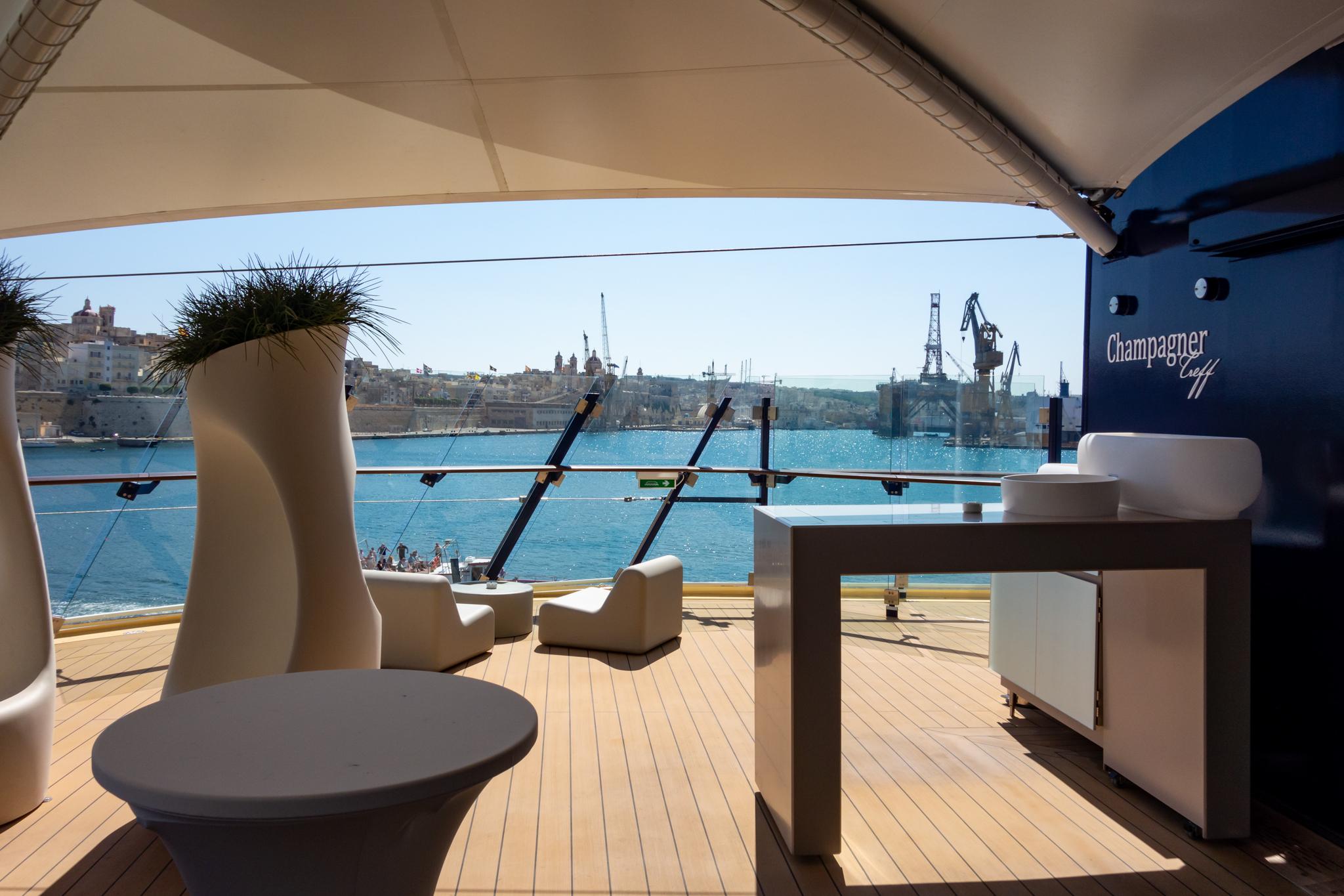 Der Kreuzfahrthafen von Valletta vom Champagnertreff auf Deck 5 gesehen. Wer mag, kann sich neben den unzähligen Dingen, die schon im Reisepreis inbegriffen sind, auch noch ein paar luxuriöse Extras gönnen. Gegen Aufpreis, versteht sich. Und obwohl das Schiff bestens gebucht war, gab es immer und zu jeder Zeit Rückzugsorte, an denen man seine Ruhe haben konnte.